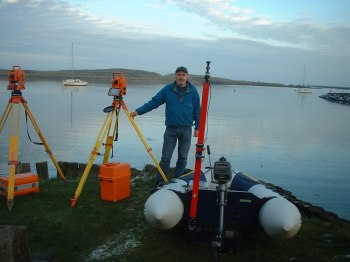 Picture of Peter Russell with a boat and surveying equipment